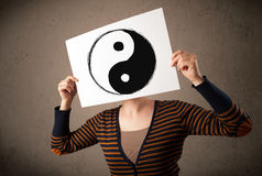 Woman holding a paper with a yin-yang on it in front of her head Stock Photos