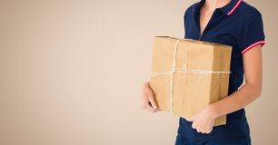 Woman holding a parcel against beige background. Mid section woman holding a parcel against beige background Royalty Free Stock Photo