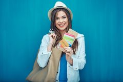 Woman holding passport with ticket for travel. Blue wall back Stock Photos