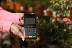 Woman holding payment terminal in floral shop, closeup. Space for text stock image