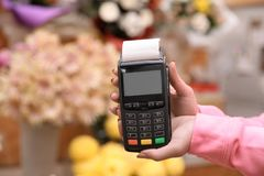 Woman holding payment terminal in floral shop, closeup. Space for text stock photos