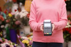 Woman holding payment terminal in floral shop, closeup. Space for text stock photography
