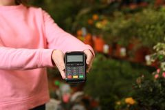 Woman holding payment terminal in floral shop, closeup. Space for text royalty free stock photo