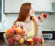 Woman holding peaches   in home kitchen. Focus on fruits Royalty Free Stock Photography