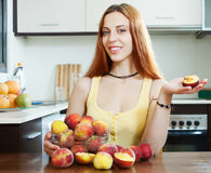 Woman holding peaches at table in home Stock Image