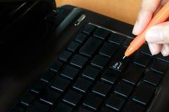 Woman holding pen with laptop pressing enter button Stock Photos