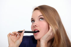 Woman holding pen to mouth Royalty Free Stock Photography