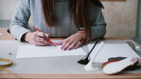 Woman holding pencil, sitting at the table and drawing sketch on paper. Erase in outline. Slider left, front view. 4K stock footage