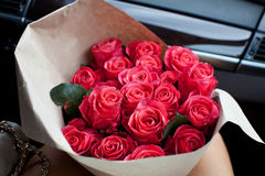 Woman holding perfect bouquet of fresh cut roses in car. Valentine day background Royalty Free Stock Photos