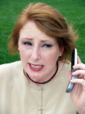 Woman holding phone. Woman holding a cell phone to ear outside Royalty Free Stock Photography