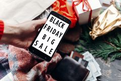 Woman holding phone with black friday big sale special offer dis. Count text on screen message on seasonal rustic background with money and bag with presents Royalty Free Stock Photos