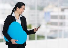 Woman holding phone and cloud in office. Digital composite of woman holding phone and cloud in office Royalty Free Stock Image