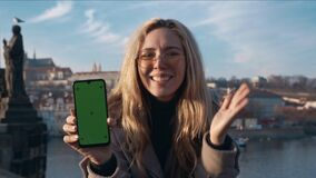 Woman holding a phone with green screen outside. Promotion, advertisement, commercial concept. Filmed on REd 4k, 10 bit