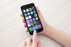 Woman holding phone iPhone 6 Space Gray over the table Royalty Free Stock Image