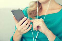 Woman holding phone and listening to music on headphones royalty free stock photography