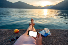 Woman holding phone lying on the pier. At beautiful sunset Stock Images