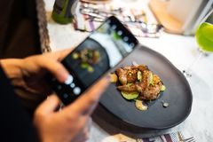 Woman holding phone and making photo of her meal royalty free stock images