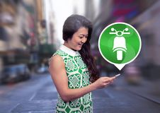 Woman holding phone with motorbike icon in city. Digital composite of Woman holding phone with motorbike icon in city Stock Photo