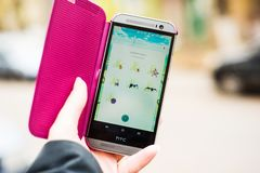 Woman holding phone and playing Pokemon Go Stock Images