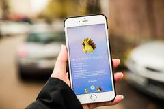 Woman holding phone and playing Pokemon Go Stock Image