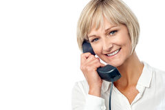 Woman holding phone receiver Stock Photography