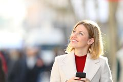 Woman holding phone thinking and looking at side. Portrait of a happy woman holding a smart phone thinking and looking at side on the street in winter Royalty Free Stock Photo