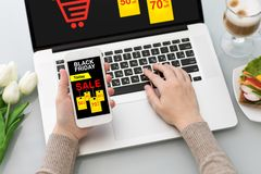 Woman holding phone and typing laptop with sale black Friday Stock Images