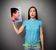 Woman holding photo of aggressive man. Startled young women holding photo of aggressive man Stock Image