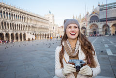 Woman holding photo camera on Piazza San Marco and looking up Stock Image
