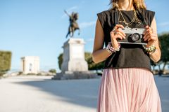 Woman traveling in Montpellier city, France. Woman holding photocamera at the famous Peyrou park in front of the Louis statue during the morning light in royalty free stock photography
