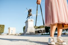 Woman traveling in Montpellier city, France. Woman holding photocamera at the famous Peyrou park in front of the Louis statue during the morning light in royalty free stock image