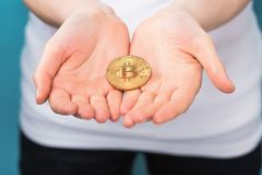Woman holding a physical bitcoin. Cryptocurrency in her hand Royalty Free Stock Image