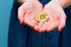 Woman holding a physical bitcoin cryptocurrency. In her hands Stock Images