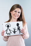 Woman holding picture with happy family Stock Photography