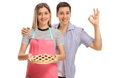 Woman holding a pie and young man making ok sign Stock Image