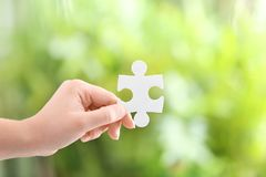 Woman holding piece of puzzle. On blurred background Stock Photography