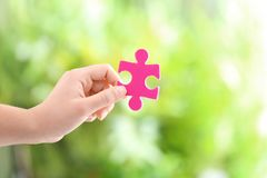 Woman holding piece of puzzle. On blurred background Stock Image