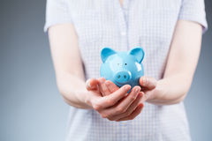 Woman Holding a Piggy Bank stock images