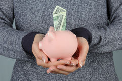 Woman holding Piggy Bank with Dollar Stock Photo