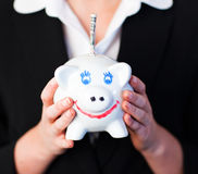 Woman Holding a piggy bank with dollars in it Royalty Free Stock Photography
