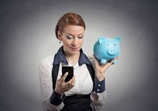 Woman holding piggy bank looking at smart phone Stock Photos