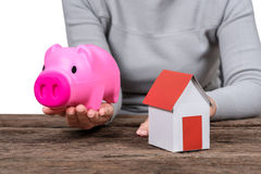 Woman holding piggy bank  and model home Royalty Free Stock Photos