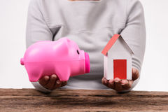 Woman holding piggy bank  and model home Stock Images