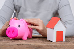 Woman holding piggy bank  and model home Royalty Free Stock Photography