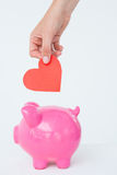 Woman holding piggy bank and red heart Royalty Free Stock Images