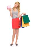Woman holding piggy bank and shopping bags Royalty Free Stock Photography