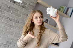 Woman holding piggy bank upside down. Royalty Free Stock Photography