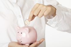 Woman holding a piggy bank on white background royalty free stock photography