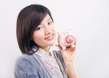 Woman holding piggybank Stock Image