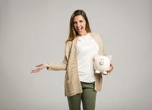 Woman holding piggybank. Beautiful and happy woman holding a piggy bank, isolated over white background Stock Photography
